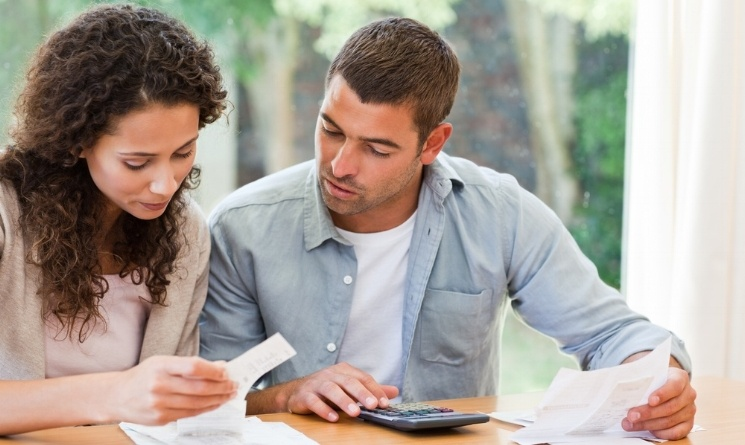 Young couple calculating their domestic bills at home-787892-edited.jpeg